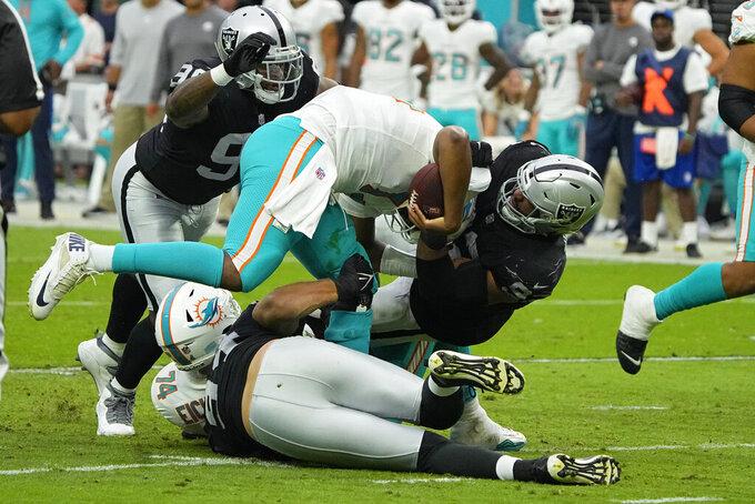 Las Vegas Raiders defensive end Solomon Thomas (92) tackles Miami Dolphins quarterback Jacoby Brissett (14) during the first half of an NFL football game, Sunday, Sept. 26, 2021, in Las Vegas. (AP Photo/Rick Scuteri)