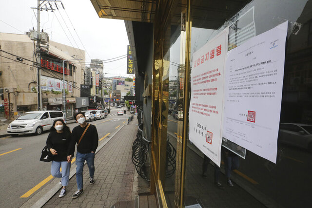 FILE - In this May 10, 2020, file photo, notices of the Seoul city emergency administrative order to prohibit gathering are posted at the entrance of a temporary closed dance club in Seoul, South Korea. The sign reads: