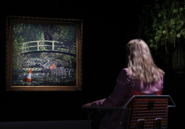 A member of staff poses in front of a work of art by Banksy entitled 'Show Me The Monet