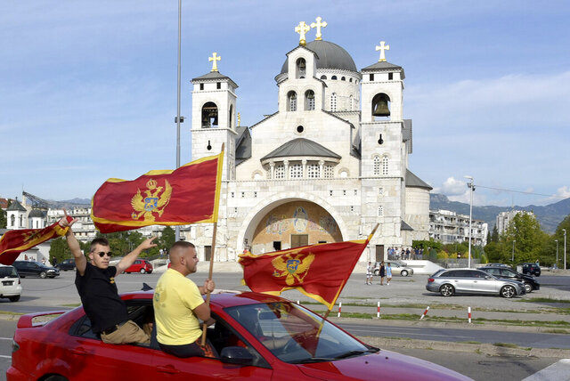 Supporters of Democratic Party of Socialists wave Montenegrin flags as they drive in front of the Serbian Orthodox Church of Christ's Resurrection in Podgorica, Montenegro, Thursday, Aug. 27, 2020. Montenegro is holding a parliamentary election this weekend with the pro-Western government facing pressure over the new coronavirus outbreak and ongoing tensions in relations with Serbia and the Serbian Orthodox Church because of a religious property law. (AP Photo/Risto Bozovic)