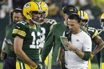 Green Bay Packers head coach Matt LaFleur talks to Aaron Rodgers during the second half of an NFL football game against the Detroit Lions Monday, Sept. 20, 2021, in Green Bay, Wis. (AP Photo/Mike Roemer)