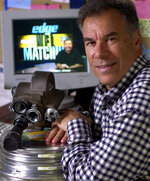 FILE - In this Sept. 26, 2000, file photo, NFL Films President Steve Sabol poses at his desk with an old 16mm movie camera while the company's new live Internet program airs on the computer screen behind him at their headquarters in Mount Laurel, N.J. Sabol was the creative force at NFL Films. Sabol joins his father, Ed, as the third father/son duo inducted into the Pro Football Hall of Fame. His father was enshrined in 2011. (AP Photo/Daniel Hulshizer, File)