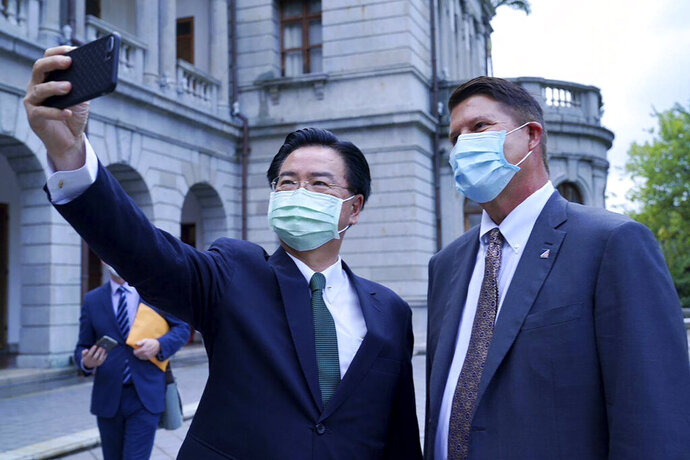 In this photo released by the Taiwan Ministry of Foreign Affairs, Taiwan's Foreign Minister Joseph Wu pose for a selfie with U.S. Under Secretary of State Keith Krach, right, during a meeting in Taipei, Taiwan, Friday, Sept. 18, 2020. China's military sent 18 planes including fighter jets over the Taiwan Strait in an unusually large show of force Monday as a U.S. envoy held a day of closed-door meetings on the self-governing island claimed by China. (Taiwan Ministry of Foreign Affairs via AP)