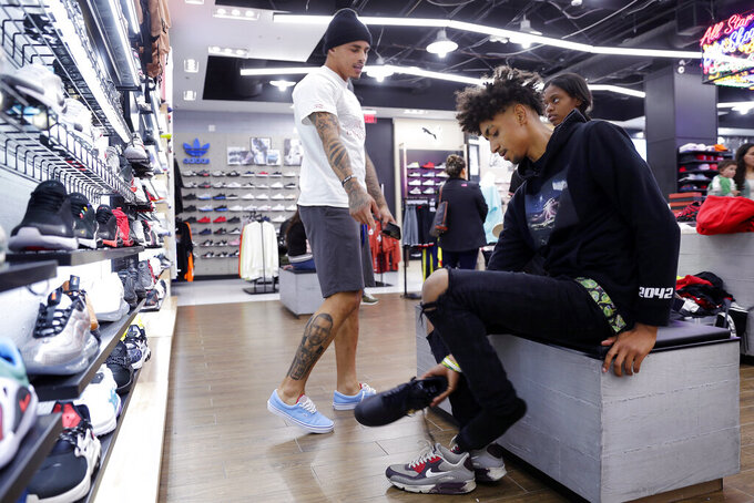 Houston Texans' Kenny Stills, left, helps Jadon Cofield, right, shop for shoes at Shoe Palace during a shopping spree Monday, Dec. 16, 2019, at Galleria Mall in Houston. Cofield and Miracle Washington-Tribble are beneficiaries of Eight Million Stories, a Houston program which helps 14-18-year-olds who have either quit or been kicked out of school continue their education, find employment and receive emotional support. (AP Photo/Michael Wyke)