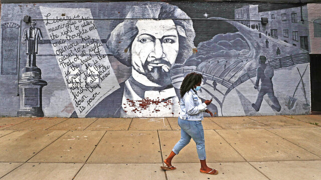 In this Wednesday, June 24, 2020, photograph, a woman walks past a mural in tribute to Frederick Douglass on the exterior wall of the Black-owned Slade's Bar and Grill in the South End neighborhood of Boston. Many from outside Boston have recently ordered takeout, purchased gift cards and supported the restaurant amid nationwide protests against racism. (AP Photo/Charles Krupa)