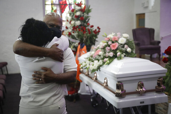 Darryl Hutchinson, facing camera, is hugged by a fellow relative during a funeral service for Lydia Nunez, who was Hutchinson's cousin, Tuesday, July 21, 2020, at the Metropolitan Baptist Church in Los Angeles. Nunez died from COVID-19. (AP Photo/Marcio Jose Sanchez)