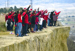 In this May 5, 2019, photo, hundreds form a line of the edge of the Billings Rimrocks for Line the Rims in Red event to honor missing and murdered indigenous people, in Billings, Mont. Reno Charette asked people to wear red and line the rim of sandstone rocks at the city park. They brought posters of men, women and children who are missing, and changed the name of the local movement to Missing and Murdered Indigenous People.  (Larry Mayer/The Billings Gazette via AP)