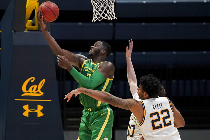Oregon forward Eugene Omoruyi, left, shoots against California forward Andre Kelly (22) and guard Ryan Betley during the second half of an NCAA college basketball game in Berkeley, Calif., Saturday, Feb. 27, 2021. (AP Photo/Jeff Chiu)
