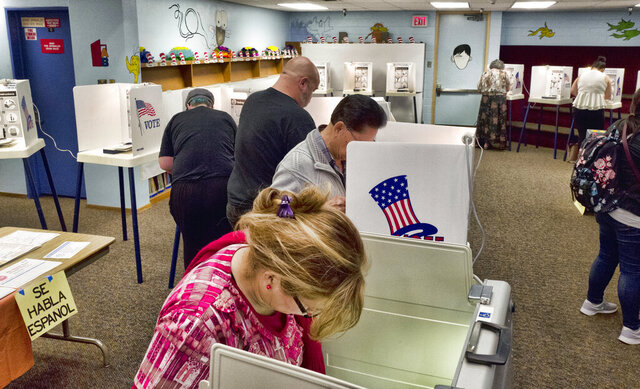 FILE - In this June 5, 2018, file photo, voters mark ballots at a polling place in the library at the Robert F. Kennedy Elementary School in Los Angeles. Californians start voting Monday, Feb. 3, 2020, in a high-profile Democratic presidential primary that has no clear front-runner. For the first time, Californians can register to vote on election day at the polls. (AP Photo/Richard Vogel, File)