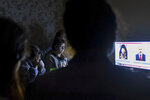 In this handout photo released by the Armenian Foreign Ministry on Monday, Sept. 28, 2020, people watch the State TV as they gather in a bomb shelter for protection against the shelling in Stepanakert, the self-proclaimed Republic of Nagorno-Karabakh, Azerbaijan. Nagorno-Karabakh authorities reported that shelling hit the region's capital of Stepanakert and the towns of Martakert and Martuni. Armenian Defense Ministry spokesman Artsrun Hovhannisyan also said Azerbaijani shelling hit within Armenian territory near the town of Vardenis. (Armenian Foreign Ministry via AP)