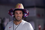 """FILE - In this Oct. 1, 2021, file photo, Philadelphia Phillies' Matt Vierling wears a straw hat after hitting a solo home run during the ninth inning of a baseball game against the Miami Marlins in Miami. Even in baseball, where traditionalists sneer at anything that might seem disrespectful or undignified, teams haven't been afraid to show some personality. The Phillies have a straw Home Run Hat, the Rockies have """"homer shades"""" sunglasses  and the Blue Jays have a blue blazer for members of their """"HR Club."""" The New York Mets ride a stuffed pony through the dugout to celebrate homers; the San Diego Padres pass around a seven-pound bejeweled necklace dubbed the """"Swagg Chain."""" (AP Photo/Lynne Sladky, File)"""