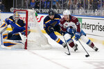 Colorado Avalanche's Brandon Saad, right, handles the puck as St. Louis Blues goaltender Jordan Binnington, left, and Colton Parayko (55) defend during the third period of an NHL hockey game Thursday, April 22, 2021, in St. Louis. (AP Photo/Jeff Roberson)