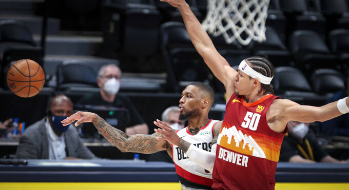 Portland Trail Blazers guard Damian Lillard (0) passes away from Denver Nuggets forward Aaron Gordon (50) in the third quarter of Game 2 of a first-round NBA basketball playoff series Monday, May 24, 2021, in Denver. (AP Photo/Joe Mahoney)