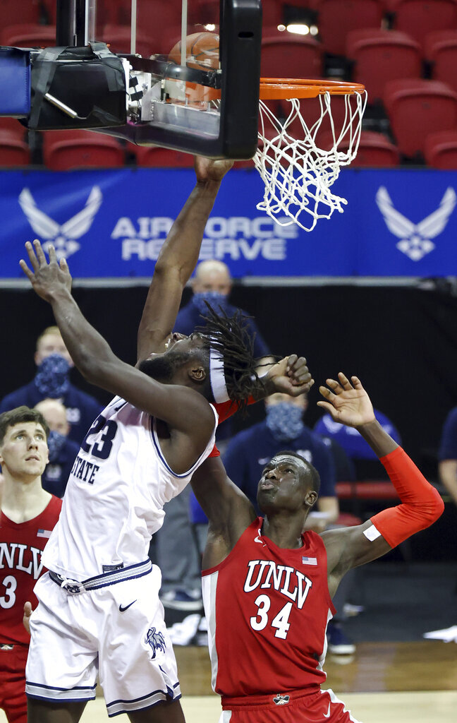Utah State center Neemias Queta (23) shoots as UNLV forward Cheikh Mbacke Diong (34) defends during the second half of an NCAA college basketball game in the quarterfinals of the Mountain West Conference men's tournament Thursday, March 11, 2021, in Las Vegas. (AP Photo/Isaac Brekken)
