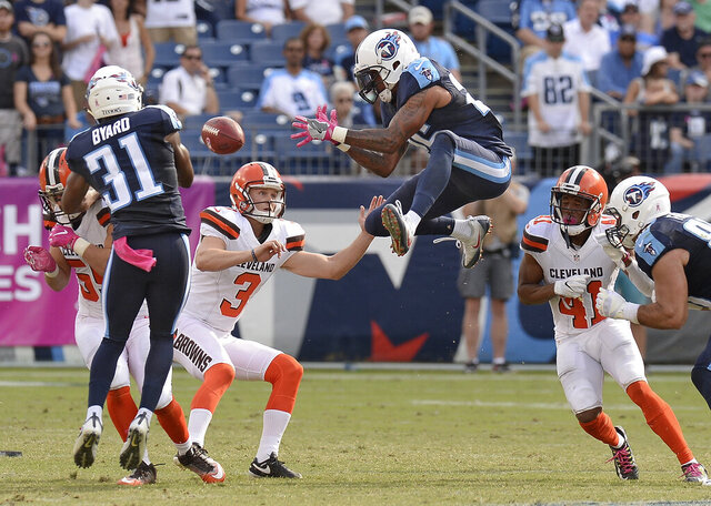 FILE - In this Oct. 16, 2016, file photo, Tennessee Titans' Rashad Johnson, center, and Kevin Byard (31) try to control an onside kick by Cleveland Browns' Cody Parkey (3) during the second half of an NFL football game in Nashville, Tenn. The Browns recovered the ball on the play. The NFL desperately is seeking ways to eliminate the more dangerous plays, and the onside kick has been deemed one. It occurs rarely, and in recent years with alterations to alignments and run-ups, the probably of it succeeding has plummeted. So Eagles owner Jeffrey Lurie suggested giving teams an alternative. They could still try the onside kick, or they could opt for a fourth-and-15 play from the kicking team's 25-yard line. (AP Photo/Mark Zaleski, File)