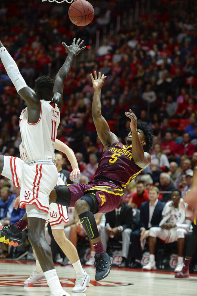 Minnesota guard Marcus Carr (5) manages a shot as Utah's Both Gach (11) defends during an NCAA college basketball game Friday, Nov. 15, 2019, in Salt Lake City. (Francisco Kjolseth/The Salt Lake Tribune via AP)