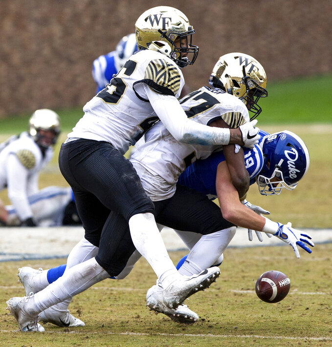 Duke's Jake Bobo (19) fumbles the ball after making a catch as Wake Forest's Nasir Greer, middle, and DJ Taylor, left, move in for a tackle during the second half of an NCAA college football game in Durham, N.C., Saturday, Nov. 24, 2018. (AP Photo/Ben McKeown)