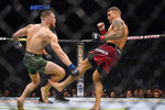 Dustin Poirier, right, kicks Conor McGregor during a UFC 264 lightweight mixed martial arts bout Saturday, July 10, 2021, in Las Vegas. (AP Photo/John Locher)