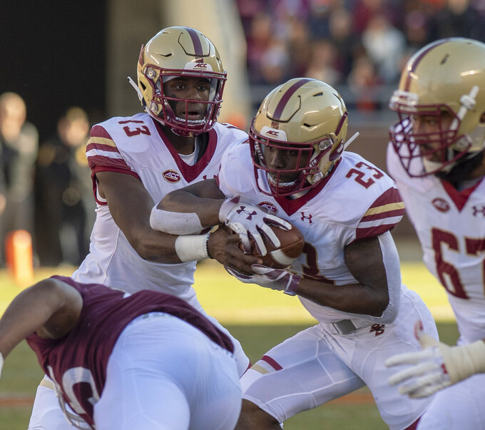 Boston College quarterback Anthony Brown hands the ball off to running back Travis Levy  during the first half of an NCAA college football game against Virginia Tech in Blacksburg, Va., Saturday, Nov. 3, 2018. (AP Photo/Matt Bell)