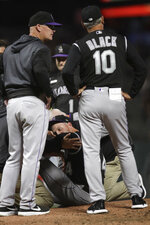 Colorado Rockies' Jeff Hoffman, center, waits to be transported off the mound after being hit by a ball batted by San Francisco Giants' Alex Dickerson, as manager Bud Black (10) stands next to him during the fourth inning of a baseball game Tuesday, Sept. 24, 2019, in San Francisco. (AP Photo/Ben Margot)