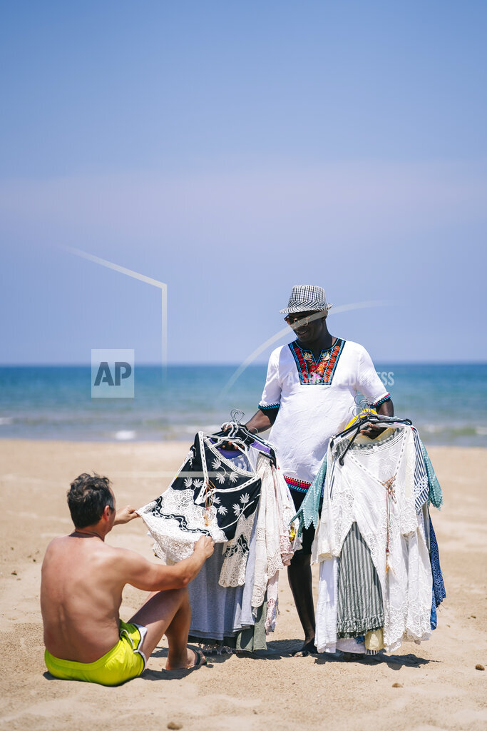 Man buying clothes from male vendor at beach during sunny day
