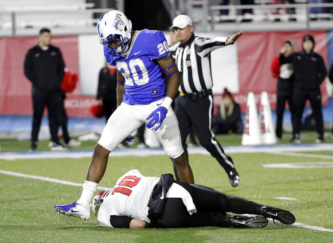 Middle Tennessee linebacker DQ Thomas (20) steps over Western Kentucky quarterback Steven Duncan (10) after knocking him down during the second half of an NCAA college football game Friday, Nov. 2, 2018, in Murfreesboro, Tenn. Middle Tennessee won 29-10. (AP Photo/Mark Humphrey)