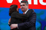 Zoran Milanovic, the liberal opposition candidate, right, hugs his spouse Sanja Music Milanovic after his headquarters claimed victory in a presidential elections in Zagreb, Croatia, Sunday, Jan. 5, 2020. A leftist Zoran Milanovic challenger won Croatia's highly contested presidential election on Sunday, beating a conservative incumbent — a rare victory by a liberal in recent votes in Central Europe. (AP Photo/Darko Bandic)