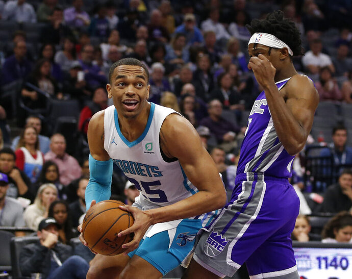 Charlotte Hornets forward PJ Washington, left, goes to the basket against Sacramento Kings guard De'Aaron Fox during the first quarter of an NBA basketball game in Sacramento, Calif., Wednesday, Oct. 30, 2019. (AP Photo/Rich Pedroncelli)