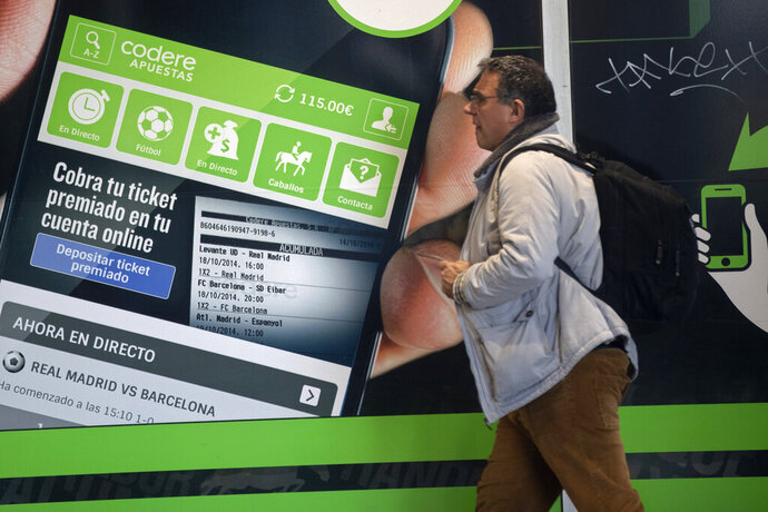 A man walks past an advertisement for online betting on the outside of a betting shop in Madrid, Spain, Friday, Feb. 21, 2020. Spain's government has announced plans to restrict advertising for on-line betting houses on the Internet, television, and during sporting events. The government said Friday that the law would be the most restrictive in the European Union. (AP Photo/Paul White)