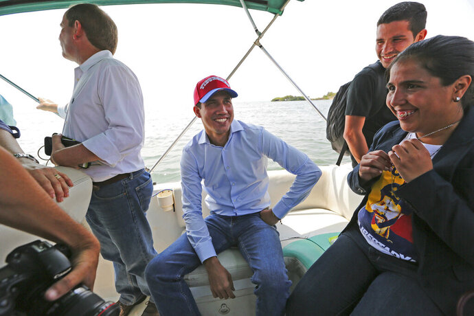 Juan Guaidó, opposition leader and self-proclaimed interim president of Venezuela, sits on a boat with staff members before crossing Maracaibo Lake to reach the town of Cabimas, Venezuela where he will lead a rally, Sunday, April 14, 2019. Guaidó was forced to take the boat in order to outmaneuver police roadblocks and reach throngs of supporters waiting to hear him speak. (AP Photo/Fernando Llano)
