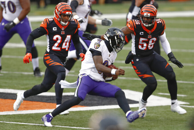 Baltimore Ravens quarterback Lamar Jackson (8) scrambles away from Cincinnati Bengals strong safety Vonn Bell (24) and middle linebacker Josh Bynes (56) during the first half the Cincinnati Bengals during the first half of an NFL football game, Sunday, Jan. 3, 2021, in Cincinnati. (AP Photo/Aaron Doster)