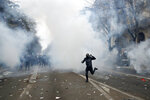 A youth runs during a demonstration in Paris, Thursday, Dec. 5, 2019. Small groups of protesters are smashing store windows, setting fires and hurling flares in eastern Paris amid mass strikes over the government's retirement reform. (AP Photo/Thibault Camus)
