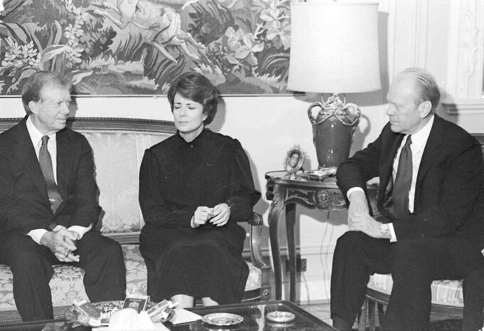 FILE - In this Oct. 9, 1981, file photo, Mrs. Jehan Sadat, widow of assassinated Egyptian President Anwar Sadat, is flanked by U.S. Presidents Jimmy Carter, left, and Gerald Ford, as they meet in her Giza Nile-side home. Jehan Sadat died in Cairo on Friday, July 9, 2021, at the age of 87, Egypt's President's office said. (AP Photo, File)
