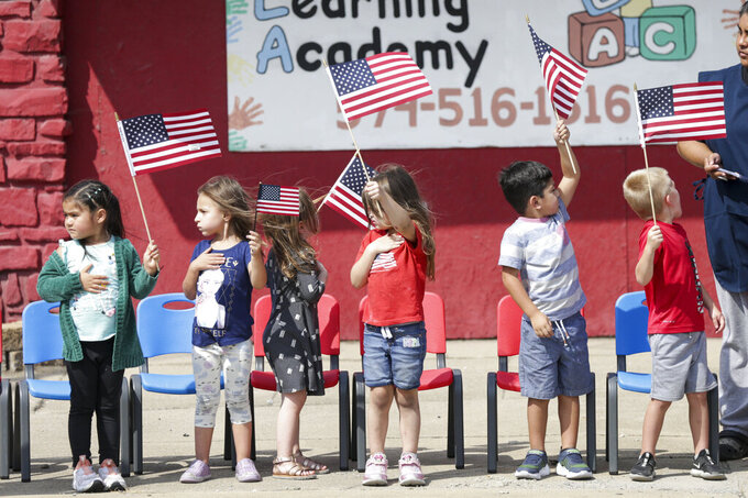 Pre-schoolers from Logansport Learning Academy save American flags in the wind during the funeral procession for Marine Cpl. Humberto Sanchez, Tuesday, Sept. 14, 2021 in Logansport, Ind. Sanchez was one of 13 U.S. service members to die in an explosion during evacuation efforts in Afghanistan. (Nikos Frazier/Journal & Courier via AP)