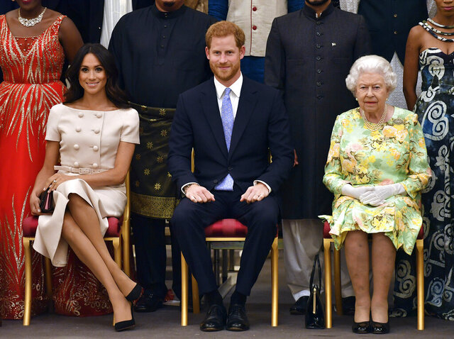 FILE - In this Tuesday, June 26, 2018 file photo Britain's Queen Elizabeth, Prince Harry and Meghan, Duchess of Sussex pose for a group photo at the Queen's Young Leaders Awards Ceremony at Buckingham Palace in London. In a stunning declaration, Britain's Prince Harry and his wife, Meghan, said they are planning
