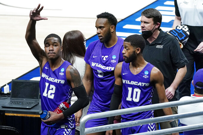 Abilene Christian's Mahki Morris (12) waves to fans as he leaves the court with Airion Simmons, center, Reggie Miller (10) and head coach Joe Golding, top right, after their 67-47 loss to UCLA in a college basketball game during the second round of the NCAA tournament at Bankers Life Fieldhouse in Indianapolis Monday, March 22, 2021. (AP Photo/Mark Humphrey)