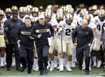 "FILE - In this Dec. 28, 2018, file photo, Purdue coach Jeff Brohm, center, leads his team onto the field for the the team's NCAA college football game in the Music City Bowl against Auburn in Nashville, Tenn. Brohm knows he has a young team. ""We have a lot to prove."" Coming off breakout freshman seasons, Purdue wide receiver Rondale Moore and Nevada running back Toa Taua headline Friday night's non-conference opener on the edge of the Sierra where both third-year coaches are anxious to turn the corner on rebuilding efforts. (AP Photo/Mark Humphrey, File)"