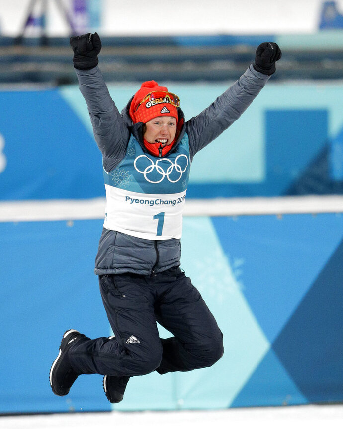 Gold medalist Laura Dahlmeier, of Germany, leaps in the air during the venue ceremony at the women's 10-kilometer biathlon pursuit at the 2018 Winter Olympics in Pyeongchang, South Korea, Monday, Feb. 12, 2018. (AP Photo/Gregorio Borgia)