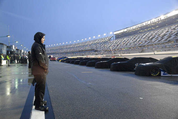 Crew members stand on pit road during a rain delay before a NASCAR Cup Series auto race was postponed to the next day at Daytona International Speedway, Saturday, July 6, 2019, in Daytona Beach, Fla. (AP Photo/Phelan M. Ebenhack)