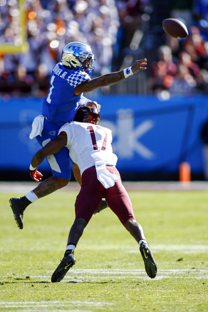 Kentucky quarterback Lynn Bowden Jr. (1) passes as he is hit by Virginia Tech defensive back Divine Deablo (17) in the first half of the Belk Bowl NCAA college football game in Charlotte, N.C., Tuesday, Dec. 31, 2019. (AP Photo/Nell Redmond)