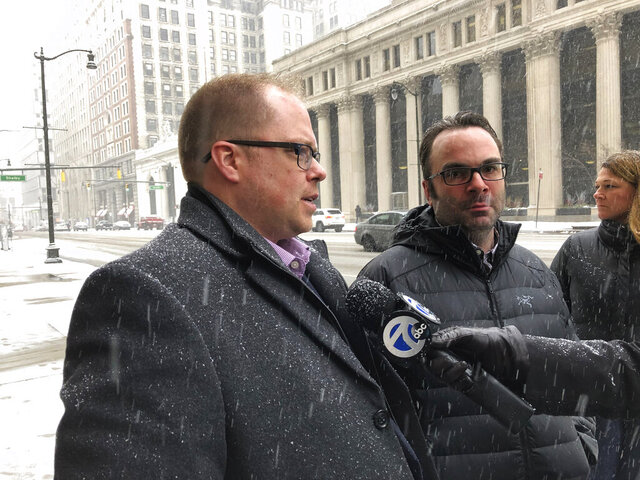 Adam Belz-Thomas, left, and husband Kyle Belz-Thomas, of Romeo, Mich., speak to reporters outside U.S. District Court in Detroit, Wednesday, Feb. 26, 2020. They were among the victims of Tara Lee, a suburban Detroit woman who was sentenced to 121 months in prison for committing fraud in arranging adoptions. (AP Photo/Ed White)