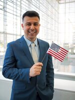 This September 2019 photo provided by Danielle Luna, shows Iraqi born refugee Bilal Alobaidi at his naturalization ceremony. Alobaidi, who arrived in the U.S. in December 2013, was resettled in Phoenix, a desert city with sweltering weather similar to that of native Mosul. The former social worker with the International Organization of Migration in Iraq now works for the nongovernmental group International Rescue Committee in Arizona, helping newly arrived refugees find apartments and jobs. (Danielle Luna via AP)