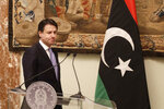 Italian Premier Giuseppe Conte walks past a Libyan flag at the end of his meeting with Libya's Prime Minister Fayez al-Sarraj at Chigi palace, in Rome, Saturday, Jan. 11, 2020. (AP Photo/Gregorio Borgia)