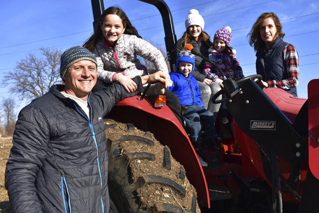 ADVANCE FOR PUBLICATION ON SATURDAY, JAN. 11, AND THEREAFTER - In this Dec. 21, 2019, photo, Adam Aberle, from left to right, Ava Aberle, Andrew Aberle, Kaylee Aberle and wife Kristina gather for a family photo on a tractor in Beloit, Wis. The family is farming hemp together. (Hillary Gavan/The Beloit Daily News via AP)