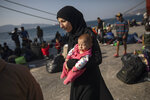 16 year-old Montaha from Aleppo, Syria, walks with her two months daughter Batour after their arrival at the port of Elefsina, near Athens, on Tuesday, Oct. 22, 2019. About 700 refugees and migrants arrived from Samos island to the port of Elefsina as authorities have been moving hundreds of migrants deemed to be vulnerable from the overcrowded Samos camp to camps on the mainland. (AP Photo/Petros Giannakouris)