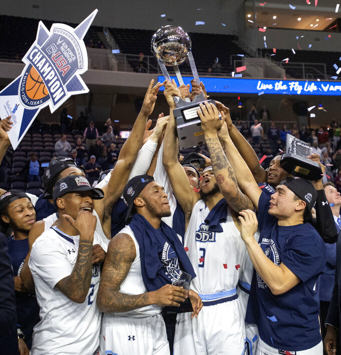 Old Dominion players hoist the trophy after defeating Western Kentucky 62-56 in an NCAA college basketball game for the Conference USA men's tournament championship Saturday, March 16, 2019, in Frisco, Texas. (AP Photo/Jeffrey McWhorter)