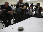 Journalists take pictures of a magnet the U.S. Navy says came from a limpet mine that didn't explode on a Japanese-owned oil tanker at a 5th Fleet base, during a trip organized by the Navy for journalists, near Fujairah, United Arab Emirates, Wednesday, June 19, 2019. Cmdr. Sean Kido of the U.S. Navy's 5th Fleet said Wednesday that the limpet mine used on a Japanese-owned oil tanker last week