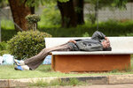 In this Jan. 9, 2019, photo, a man lies on a bench outside a government hospital after being turned away during the doctors strike at Parirenyatwa Hospital, in Harare, Zimbabwe. A doctors strike in Zimbabwe has crippled a health system that was already in intensive care from neglect. It mirrors the state of affairs in a country that was full of promise a year ago with the departure of longtime leader Robert Mugabe but now faces economic collapse.(AP Photo/Tsvangirayi Mukwazhi)