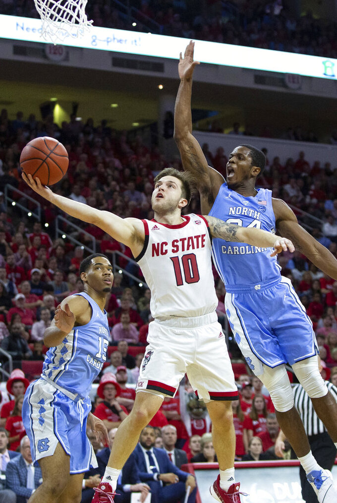 North Carolina State's Braxton Beverly (10) attempts a layup ahead of North Carolina's Kenny Williams, right, during the first half of an NCAA college basketball game in Raleigh, N.C., Tuesday, Jan. 8, 2019. (AP Photo/Ben McKeown)