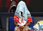 Japan's Naomi Osaka sits with her towel over her head during a break in her third round loss to Coco Gauff of the U.S. at the Australian Open tennis championship in Melbourne, Australia, Friday, Jan. 24, 2020. (AP Photo/Lee Jin-man)